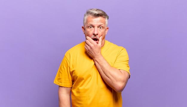 Alter älterer mann mit weit geöffnetem mund und augen und hand am kinn, unangenehm schockiert, sagt was oder wow