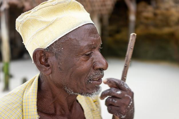 Alter afrikanischer hirte, der am strand mit stock spazieren geht
