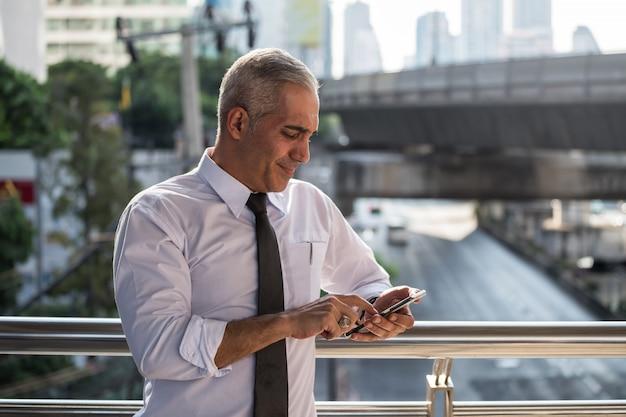 Alter amerikanischer geschäftsmann benutzt smartphone in der stadt