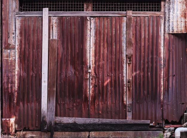Alter ausführlicher gealterter rostiger gewölbter rotbrauner strukturierter zinkaußenblech-außenzaun der rostbraunen struktur, der in der bauindustrie als hausbaumaterial verwendet wurde.