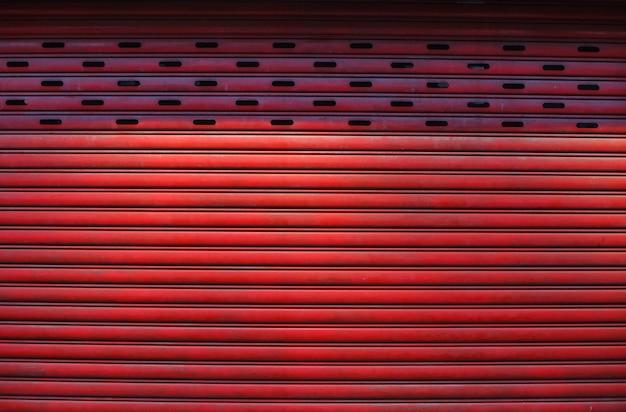 Alter ausführlicher gealterter roter strukturierter zinklegierungsmetallrolltor der weinlese, der vordere außendesign des speichers benutzt in der bauindustrie als baumaterial.