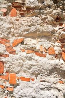Alter backsteinmauerhintergrund mit rustikalem beton, rissen und natürlichem licht