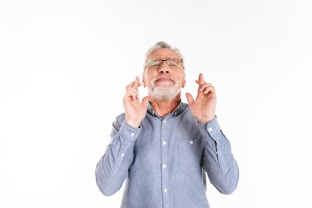 Alter bärtiger mann, der gebetsgeste macht und mit geschlossenen augen isoliert aufschaut