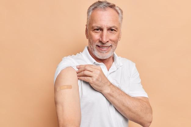 Alter bärtiger mann, der gegen coronavirus geimpft wurde, zeigt arme mit klebepflaster, die sich während pandemie-posen gegen braune wand um gesund kümmern