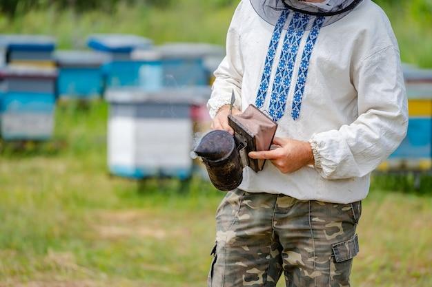 Alter bienenraucher. werkzeug des imkers. alles für einen imker, um mit bienen zu arbeiten. bienenraucher in den händen der imker.