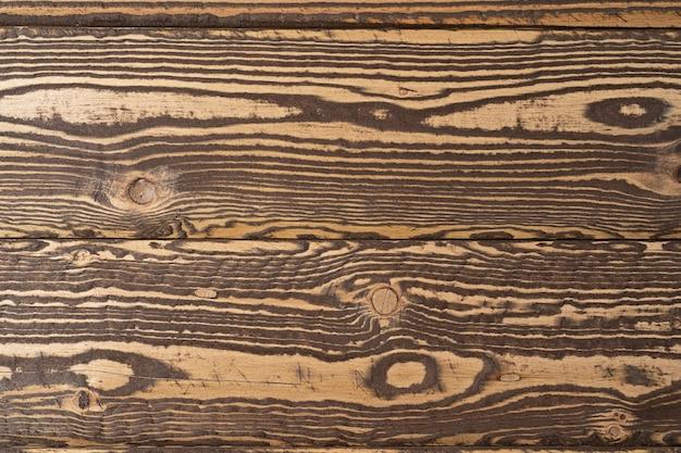Alter brauner holzhintergrund aus dunklem naturholz im grunge-stil natürliche rohe gehobelte textur aus nadelkiefer die oberfläche des tisches mit kopienraum für text