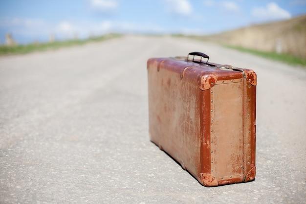 Alter brauner koffer steht auf einer wüstenstraße