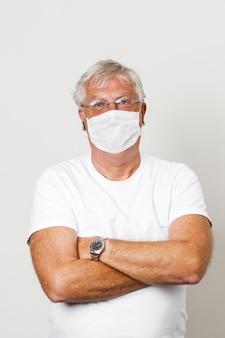 Alter britischer kerl, der durch koronavirus gefährdet ist alter alter grauer haartyp, der eine gesichtsmaske zum schutz gegen koronavirus trägt halbkörperansicht des mann-augenglases in blasser weißer wand mit platz für text covid