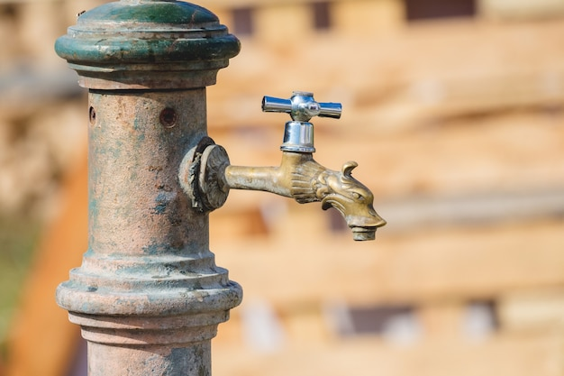 Alter bronze-wasserhahn im freien bei sonnigem wetter, geschlossen