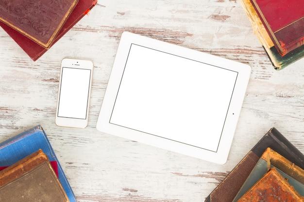 Alter bücherrahmen mit tablette und telefon