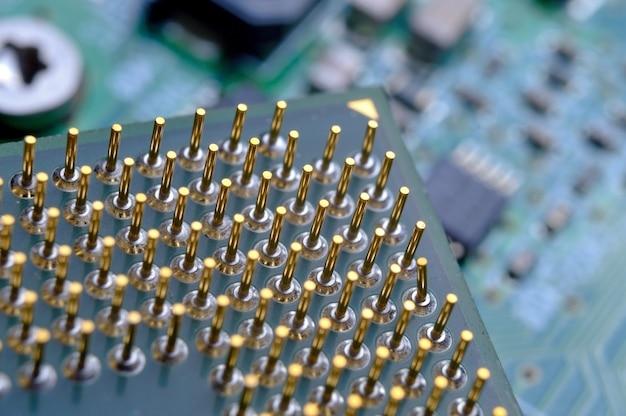 Alter computerprozessor mit vergoldeten beinen, mikroschaltungen darauf, supermakrofoto