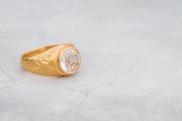 Alter diamantring der nahaufnahme auf unscharfem zementbodenhintergrund