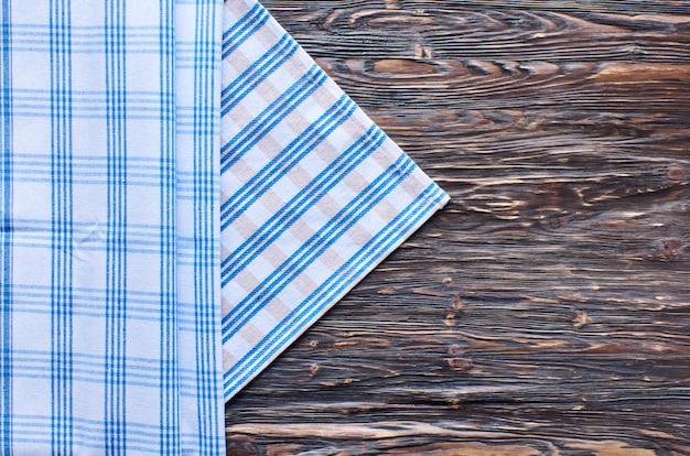 Alter dunkler hölzerner hintergrund. holztisch mit blau-weißem küchentuch