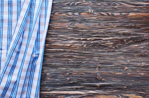 Alter dunkler hölzerner hintergrund. holztisch mit blauen küchentüchern