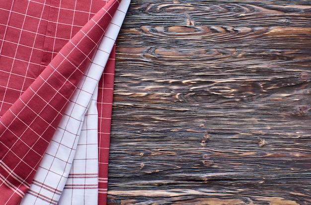 Alter dunkler hölzerner hintergrund. holztisch mit roten und weißen küchentüchern