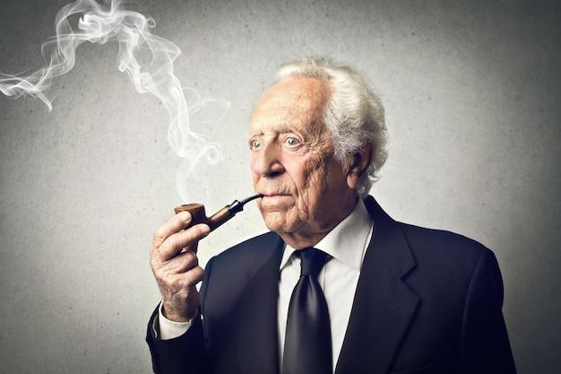 Alter eleganter mann, der eine pfeife raucht