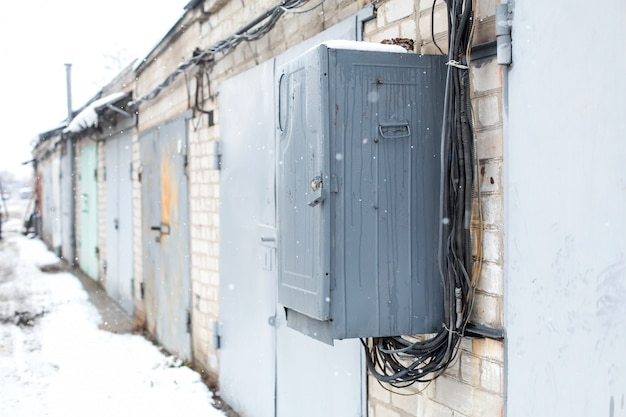 Alter elektrischer kommunikationskasten, der an einer wand in einer garagengenossenschaft hängt