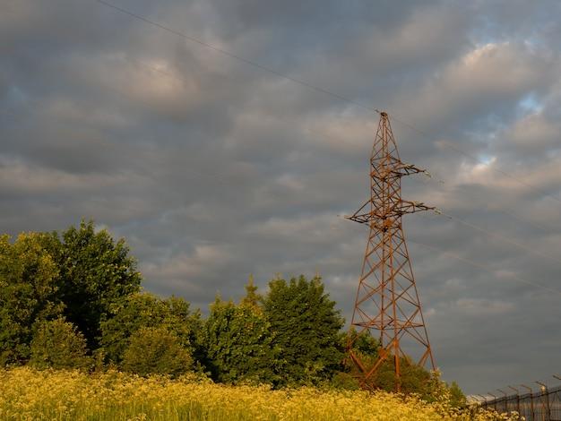 Alter elektrischer turm und elektrisches kabel auf einem feld auf dem land mit bewölktem und blauem himmel.