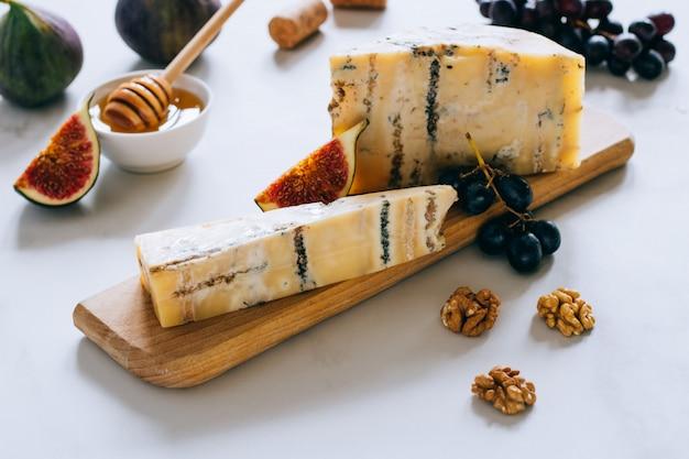 Alter englischer stilton käse. blauschimmelkäse, feigen und trauben auf einem marmorschneidebrett