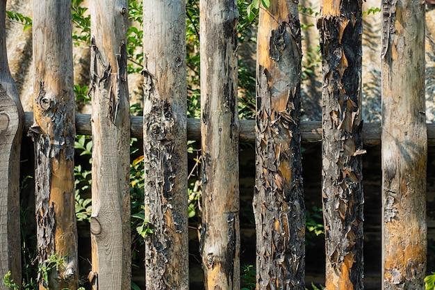 Alter fauler zaun, der den garten einschließt. textur der bretter