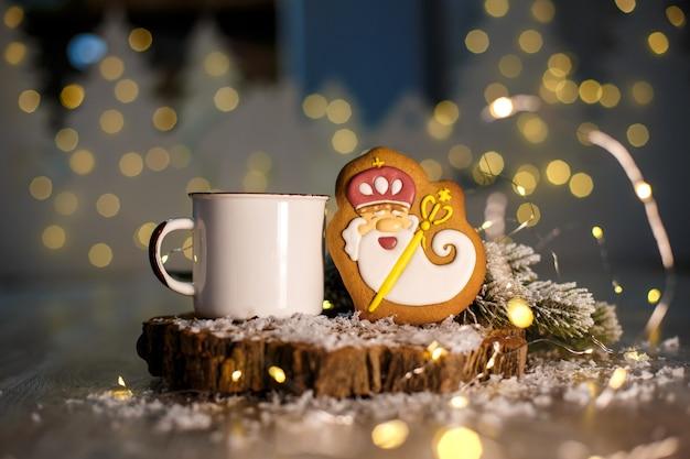 Alter freundlicher zauberer des lebkuchens in der gemütlichen dekoration mit girlandenlichtern und tasse heißem kaffee
