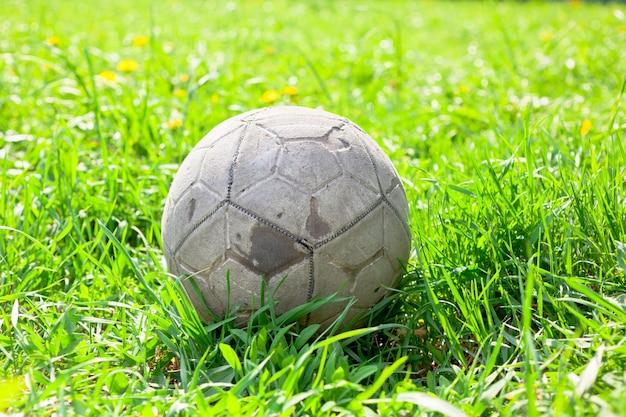 Alter fußball auf dem grünen gras