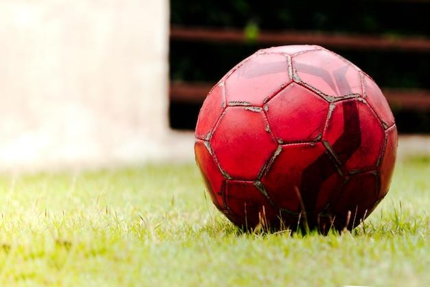 Alter fußball auf fußballplatz des grünen grases