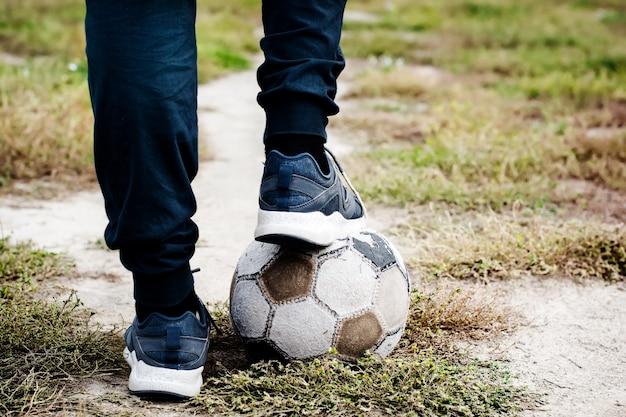 Alter fußball mit seinen füßen auf dem fußballplatz. selektiver fokus.