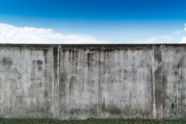Alter gebrochener grauer zement oder betonmauer mit blauem himmel als hintergrund. schmutz vergipster strukturierter hintergrund des stucks.