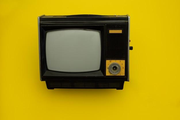 Alter gefäß fernsehapparat auf einem gelb.