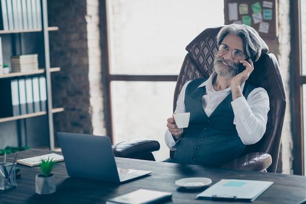 Alter geschäftsmann, der im büro ruht, hält kaffeetasse, die am telefon spricht