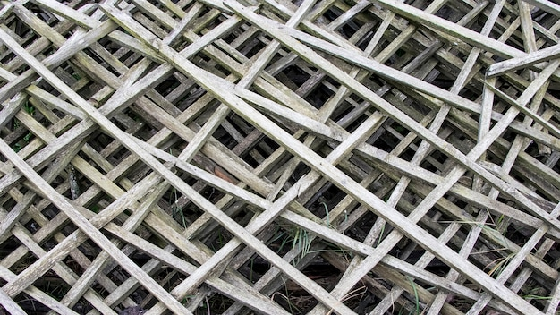 Alter grauer diagonaler holzrost. alter zaun aus holzgittern. hintergrund.