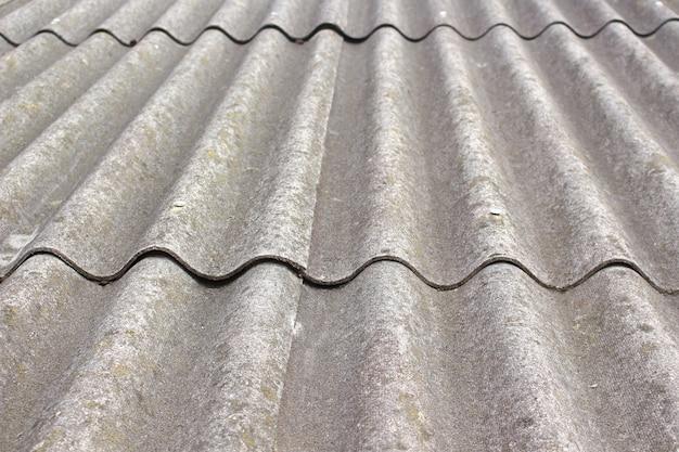 Alter grauer schiefer auf dem dach der scheune.