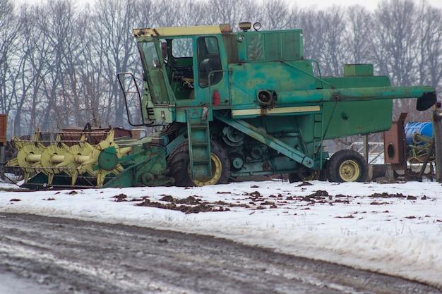 Alter grüner mähdrescher auf einem schneebedeckten feld.