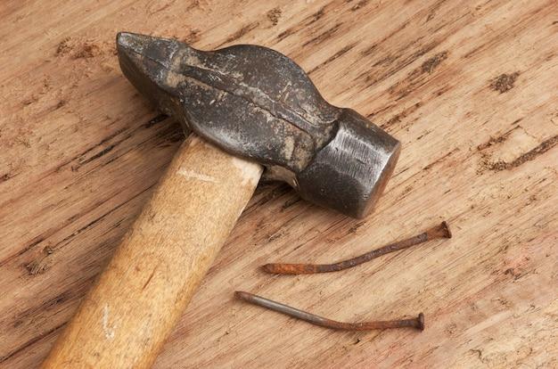 Alter hammer und ein rostiger nagel auf einer tafel