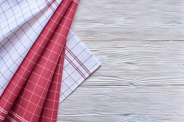 Alter heller hölzerner hintergrund. holztisch mit roten und weißen küchentüchern