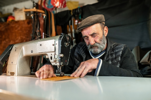 Alter hipster-bärtiger mann mit flacher kappe, die leder mit nähmaschinen-handwerkskonzept arbeitet