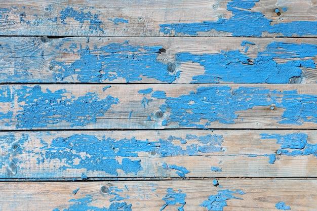 Alter hölzerner hintergrund mit schäbiger blauer farbe der flocken in flachem lay
