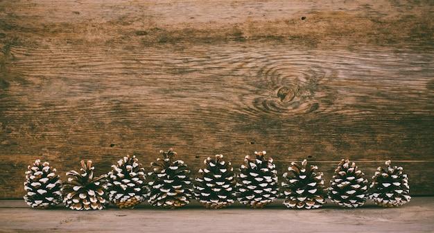 Alter hölzerner hintergrund mit tannenzapfen. das konzept eines neuen jahres weihnachten