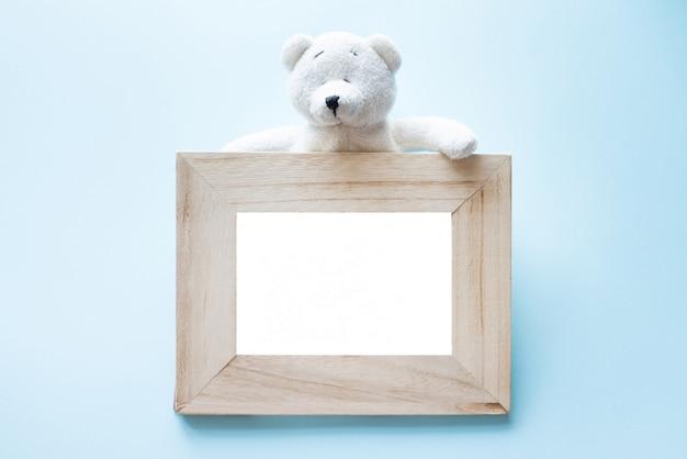 Alter hölzerner rahmen des fotos mit dem einzelnen weißen teddybären, der auf blau sitzt.