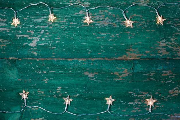 Alter hölzerner rustikaler weihnachtshintergrund mit sternförmigen lichtern.