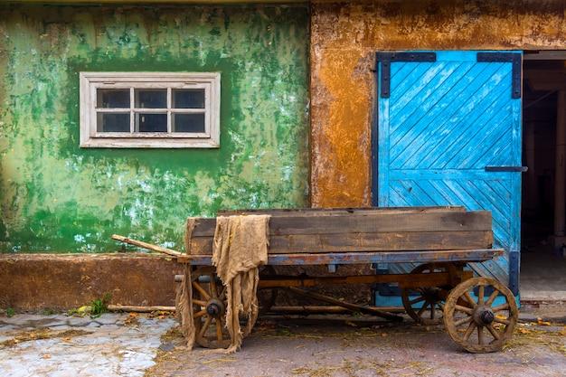 Alter hölzerner wagen im dorf auf dem hintergrund eines alten hauses. großes blaues holztor.
