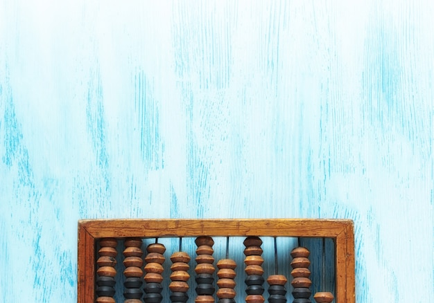Alter hölzerner zerkratzter weinlese-dezimalabakus auf einem blauen holzbrett
