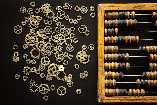 Alter hölzerner zerkratzter weinlese-dezimalabakus und steampunk-zahnräder auf einem schwarzen schreibtisch