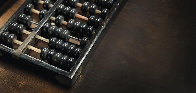 Alter holz-arbacus für taschenrechner-lernwerkzeug auf holzhintergrund mit fahnengröße