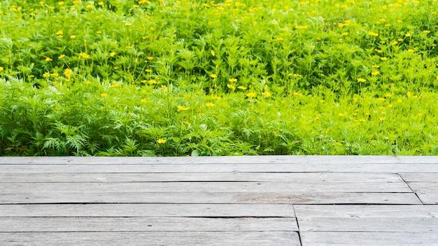 Alter holzboden mit gelben kosmosblumenfeldern