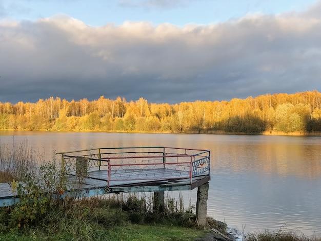 Alter holzsteg über stillem seewasser mit herbstlichen gelben waldbäumen im horizont