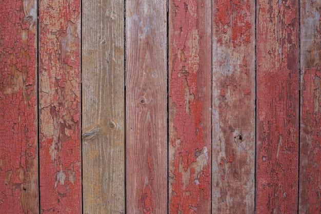 Alter holzzaun in roter, abblätternder rissiger farbe gemalt. textur der roten holzbretter, alte scheunenwand, rustikaler stil