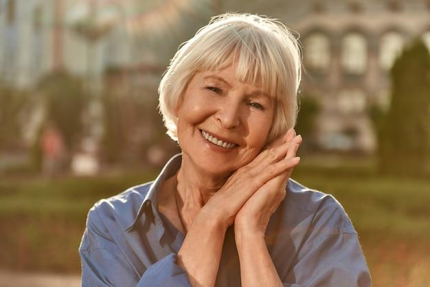 Alter ist nur ein zahlenporträt einer glücklichen und schönen älteren frau, die in die kamera schaut und lächelt
