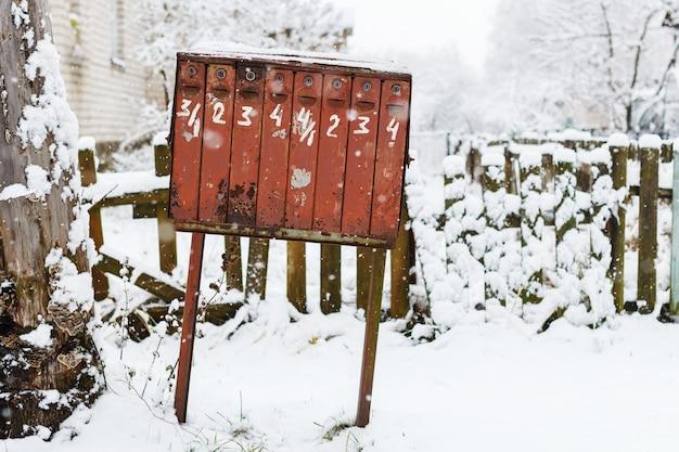 Alter klappriger briefkasten im winter unter dem schnee